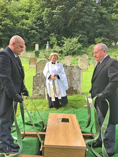 Representatives of F.A. Stockill and Son Funeral Directors and The Rev. Dr. Jo White at the burial. Photo by Claire Potter