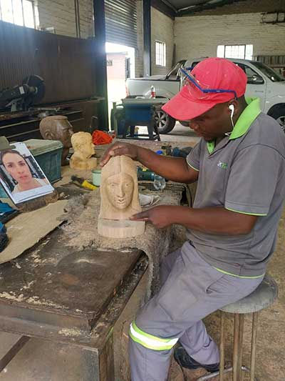 A craftsman carves detail into a memorial sculpture at South Africa-based African Custom Sculptures. Photo provided by Steve Parsons