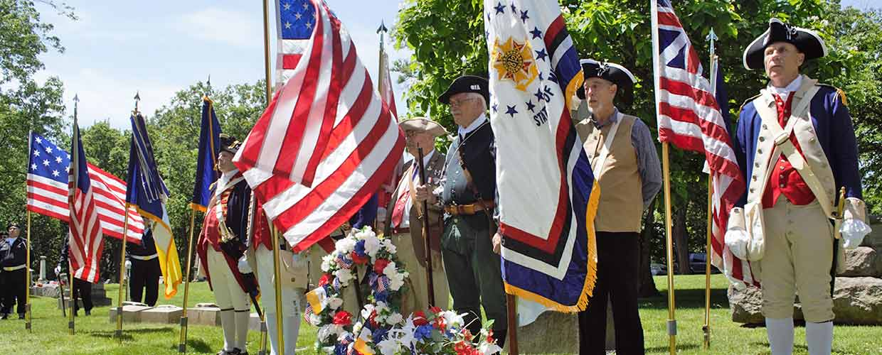Members of the Michigan Society Sons of the American Revolution color guard perform military honors over the grave of Pvt. James Robinson, an African-American hero of the Revolutionary War and War of 1812 at Elmwood Cemetery, Detroit, Mich., June 22, 2019 (Michigan National Guard Photo by 1st Lt. Andrew Layton).